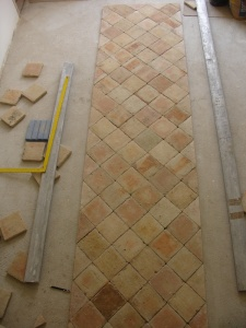 Préparée au sol, la crédence de la cuisine composée de tomettes du XVIIe siecle